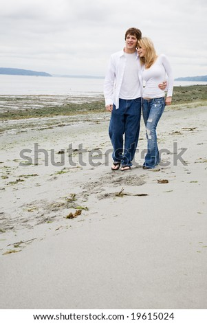 A beautiful caucasian couple in love walking on the beach - stock photo