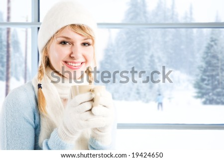 A beautiful caucasian girl drinking hot coffee at a ski resort during a snowy day