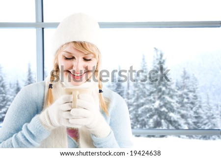 A beautiful caucasian girl drinking hot coffee at a ski resort on a snowy day - stock photo