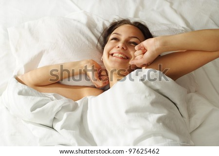 A beautiful caucasian girl in bed on a light background