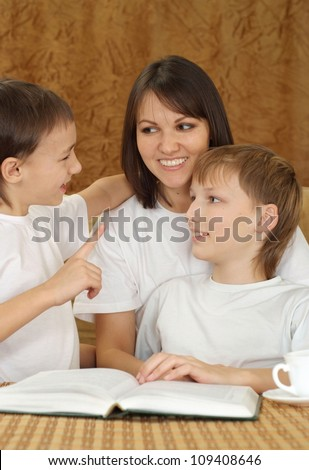 A beautiful Caucasian mama with her son sitting on the couch on a light background - stock photo