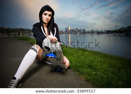 A beautiful caucasian skater teen girl outdoor during the sunset - stock photo