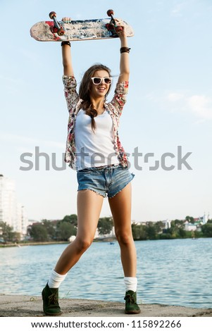 A beautiful caucasian skater woman during the sunset, outdoor - stock photo