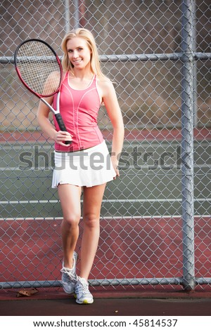 A beautiful caucasian tennis player on the tennis court - stock photo
