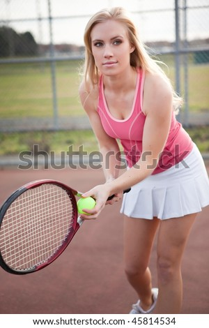 A beautiful caucasian tennis player serving the ball on the tennis court - stock photo