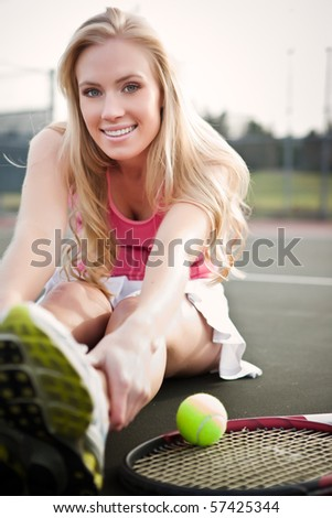 A beautiful caucasian tennis player stretching on the tennis court - stock photo