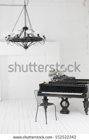 A beautiful chandelier and a piano in the room with white floors and walls - stock photo