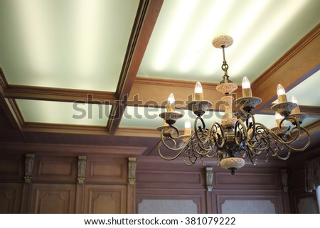 A beautiful chandelier with candlesticks in the interior of the room in the English style - stock photo