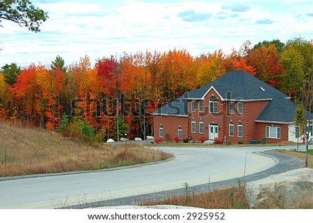 A beautiful colinial house against vibrant autumn colors - stock photo