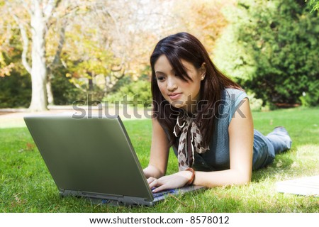 A beautiful college student working on her laptop on campus - stock photo