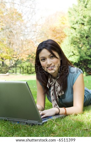 A beautiful college student working on her laptop outdoor - stock photo