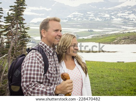 A beautiful couple hiking together high in the mountains - stock photo
