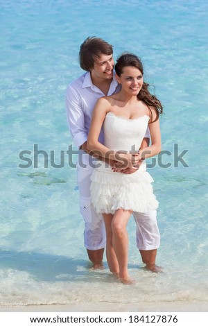 A beautiful couple is standing on the beach - stock photo
