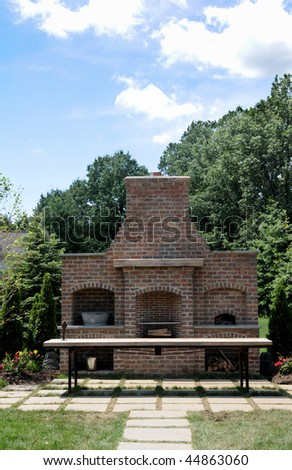 A beautiful custom outdoor fireplace and grill - stock photo