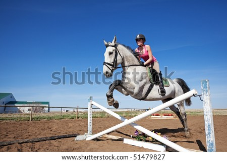 A beautiful, dappled gray horse with rider,  jumping a hurdle. - stock photo