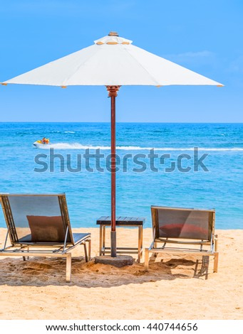 A beautiful day at the beach with sun lounger chairs under an umbrella and a Jet Ski zooming past in the distance.