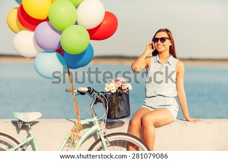 A beautiful day for a ride. Smiling young women talking on the mobile phone while sitting on parapet near the bicycle with balloons - stock photo