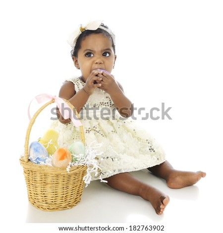 A beautiful, dressed up baby girl, and Easter basket by her side.  She's making a face as she tries to bite one of the Easter eggs.  On a white background. - stock photo