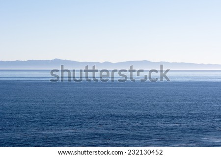 A beautiful early morning view of Santa Cruz Island in Santa Barbara with a slight pink inversion layer lining the horizon from cold weather - stock photo
