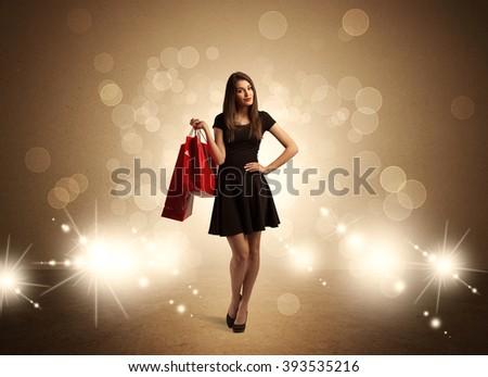 A beautiful elegant woman in black standing with red shopping bags in front of brown background and bright glowing lights concept - stock photo