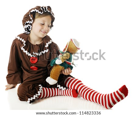 """A beautiful elementary """"gingerbread girl"""" admiring her gingerbread doll.  On a white background. - stock photo"""