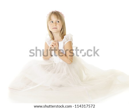 A beautiful elementary girl in white, hands clasped while looking heavenward.  On a white background.