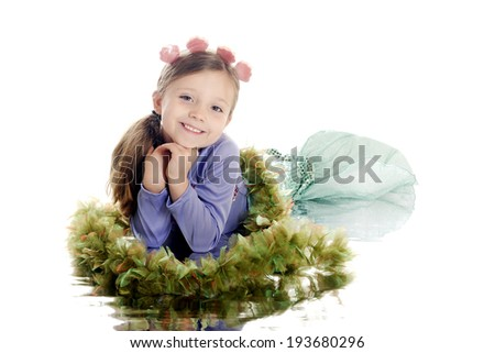 A beautiful elementary mermaid surrounded by seaweed with a watery reflection.  On a white background. - stock photo