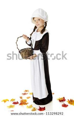 A beautiful elementary Pilgrim girl holding a basketful of the acorns she's collected.  She's surrounded by colorful fall leaves.  On a white background. - stock photo