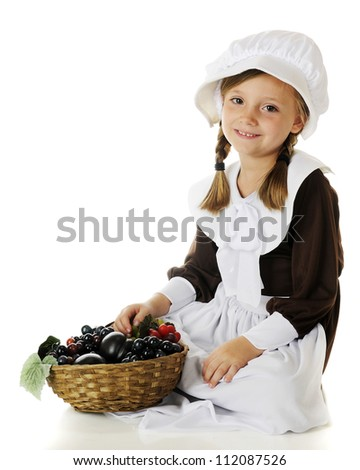 A beautiful elementary Pilgrim girl sitting with a basketful of fruit.  On a white background. - stock photo