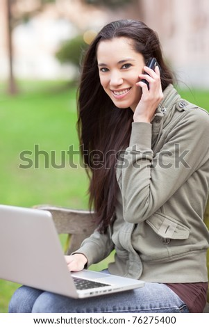 A beautiful ethnic college student talking on the phone working on her laptop on campus - stock photo