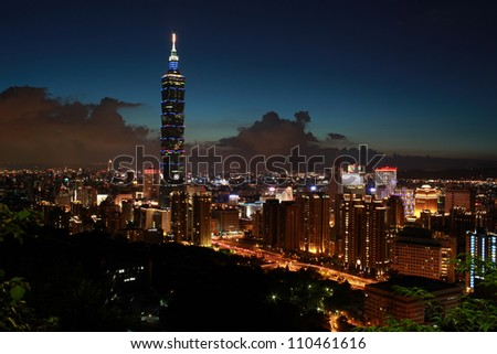 a beautiful Evening of Taipei city and Taipei 101 with silhouette of a mountain in front - stock photo