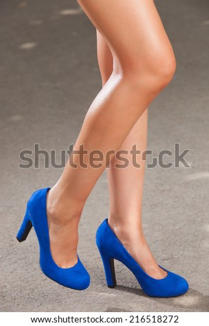 A beautiful female legs with blue shoes  - stock photo