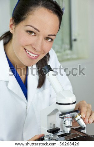 A beautiful female medical or scientific researcher using her microscope in a laboratory. - stock photo