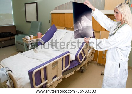 A beautiful female radiologist examining an x-ray - stock photo