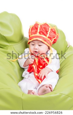 A beautiful five month year old baby boy wearing a   buddhist monk on white background.