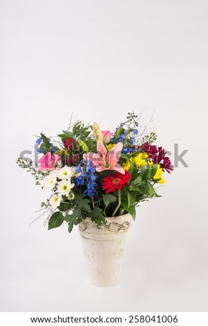 A beautiful flower arrangement in a vase set on a white isolated background. - stock photo