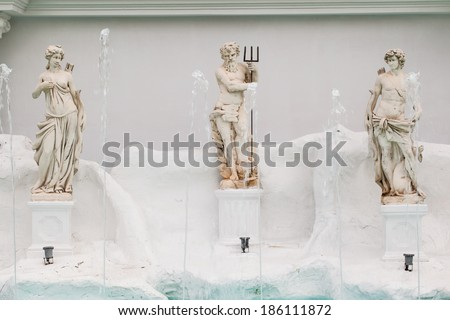 a beautiful fountain with statues and rocks - stock photo