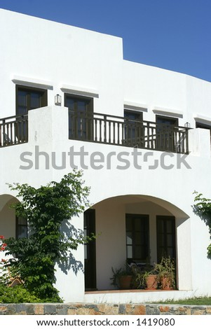 A beautiful front entrance to a greek villa with bright blue sky - stock photo