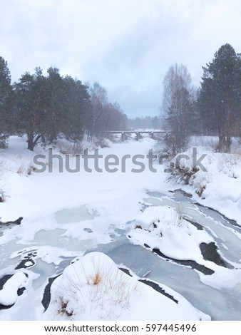A beautiful frozen river and snow go and a bridge in the distance, Russia.