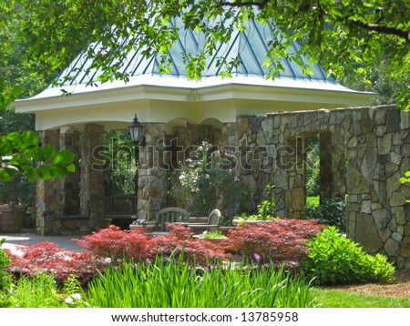 A beautiful garden structure with overhead pavilion and natural stone columns.  The garden showcases wonderful textures in plant selections.
