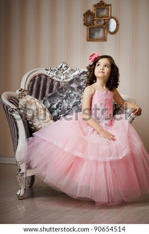 A beautiful girl, a child on a chair in a nice dress - stock photo