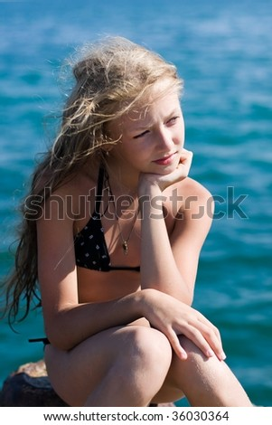 A beautiful girl at the beach, looking at the ocean. - stock photo