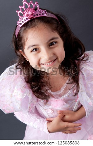 A beautiful girl child smiles as she dresses in her princess costume