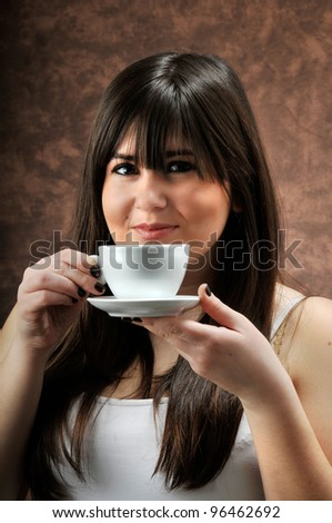 a beautiful girl holds a cup of coffee - stock photo