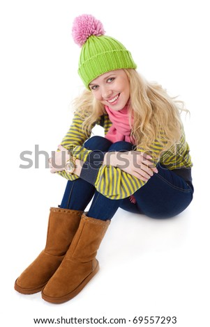 a beautiful girl in a funny cap is sitting on a floor. isolated on a white background - stock photo
