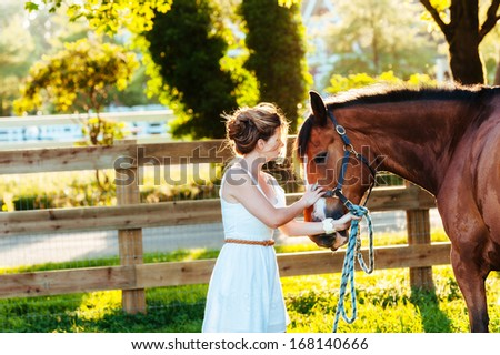 a beautiful girl in a white dress and her horse - stock photo