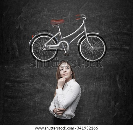 A beautiful girl in formal clothes is dreaming about a new bicycle. A sketch of a bicycle is drawn on the black chalkboard. - stock photo