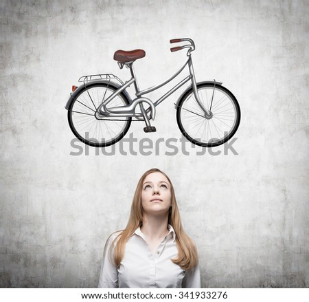 A beautiful girl in formal clothes is dreaming about a new bicycle. A sketch of a bicycle is drawn on the concrete wall. - stock photo