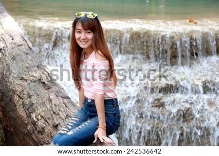A beautiful girl sits on a log bridge across a creek with waterfall as background at Erawan waterfall in Kanchanaburi, Thailand - stock photo