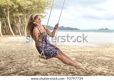 A beautiful girl swings and laughs on a beach in Hawaii - stock photo
